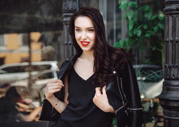 Stilvoller modischer langhaariger mädchen-hipster in schwarzer kleidung. sinnliche frau der hübschen jungen sexy mode im schwarzen kleid und in der lederjacke, die gegen straße, städtischer kleidungsstil aufwirft. strassenfotografie.