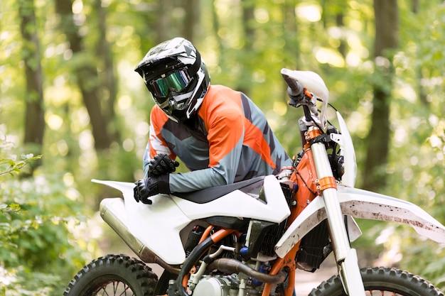 Stilvoller motorradfahrer, der im wald aufwirft