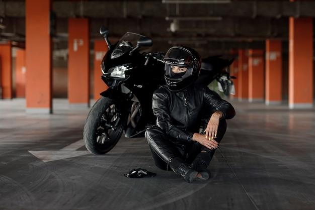 Stilvoller motorradfahrer der jungen frau mit den schönen augen in der schwarzen schutzausrüstung und im vollgesicht