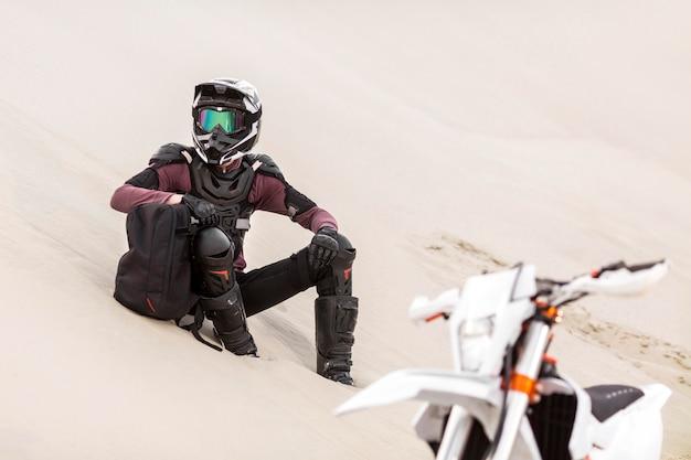 Stilvoller motorradfahrer, der sich in der wüste entspannt