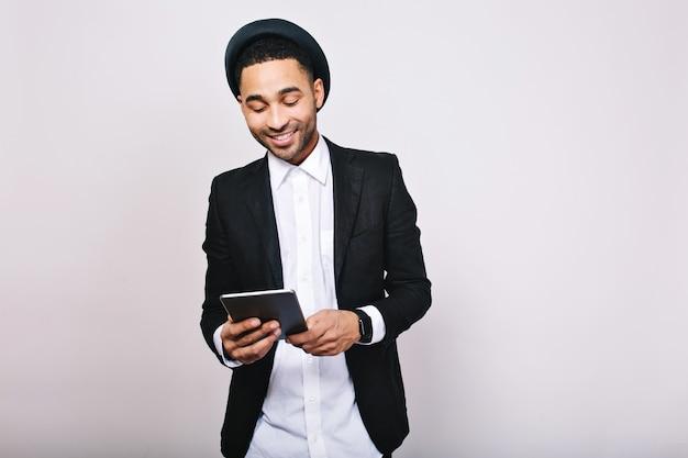 Stilvoller porträt eleganter schöner mann im weißen hemd und in der schwarzen jacke mit tablette. geschäftsmann, großer erfolg, arbeit, fröhliche stimmung, lächelnd