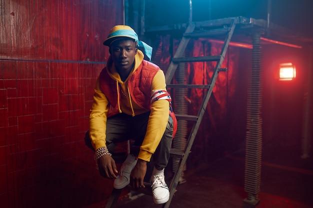 Stilvoller rapper posiert auf der treppe im grunge-studio mit cooler unterirdischer dekoration. hip-hop-performer, rap-sänger, breakdance