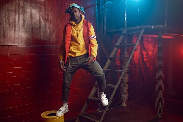 Stilvoller rapper posiert auf der treppe im grunge-studio mit cooler unterirdischer dekoration