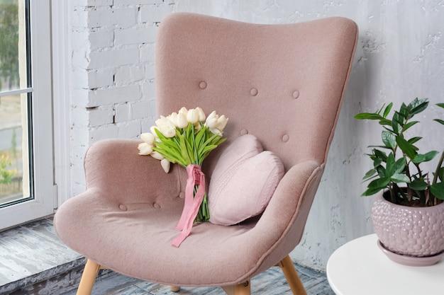Stilvoller rosa sessel mit herzförmigem kissen und tulpenstrauß in einem hellen minimalistischen innenraum.