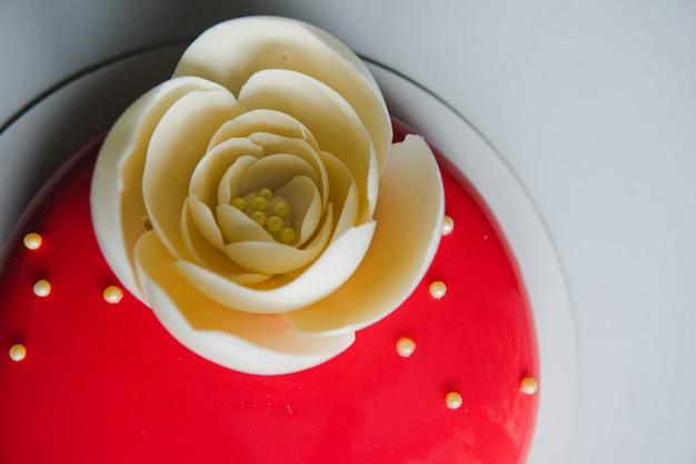 Stilvoller roter kuchen mit weißer rose. roter kuchen mit einer großen blume der weißen schokolade. geburtstagskuchen