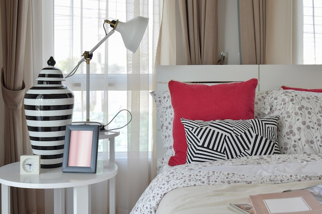 Stilvoller schlafzimmerinnenraum mit blumenmusterkissen und dekorativer tischlampe