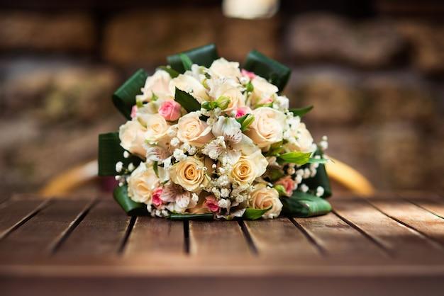 Stilvoller, schön verzierter hochzeitsblumenstrauß von gelben und rosafarbenen rosen auf holztisch.