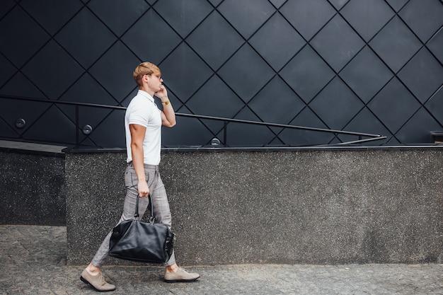 Stilvoller schöner mann, der auf der straße nahe modernem schwarzem gebäude geht.