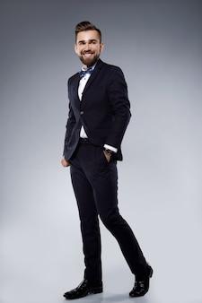 Stilvoller schöner mann, der einen klassischen anzug mit fliege trägt