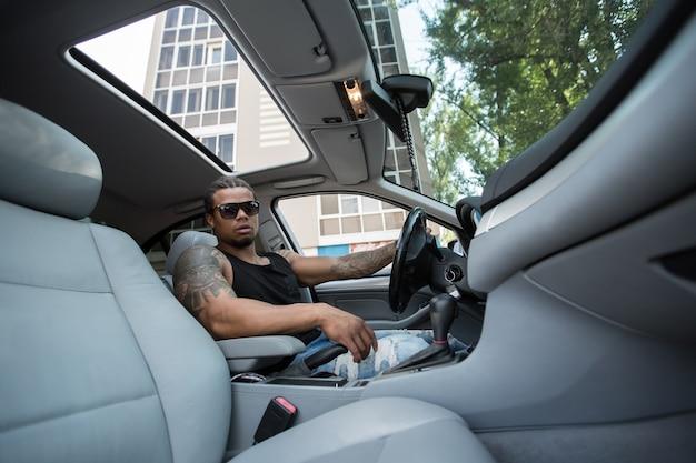 Stilvoller schwarzer mann, der hinter dem lenkrad des luxusautos sitzt