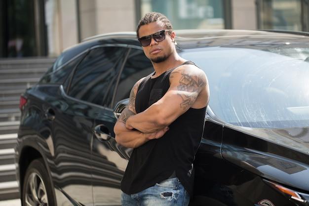 Stilvoller schwarzer mann, der neben seinem schicken auto steht