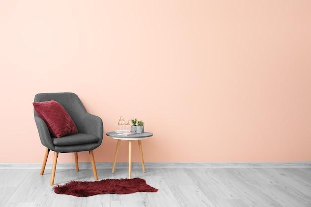 Stilvoller sessel mit kissen und tisch nahe farbwand im raum