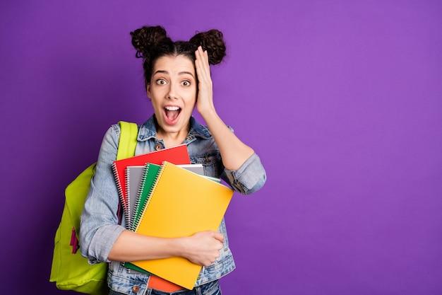 Stilvoller student mit dem lockigen haar, das gegen die lila wand aufwirft