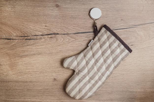 Stilvoller topflappen, der an einem haken auf hölzerner wand in der küche hängt. haken kleben