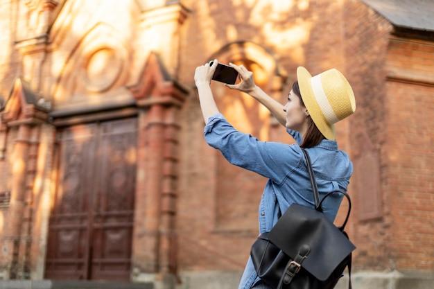 Stilvoller tourist mit hut, der bilder im urlaub macht