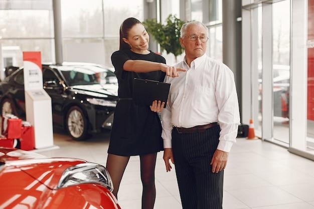 Stilvoller und eleganter alter mann in einem autosalon