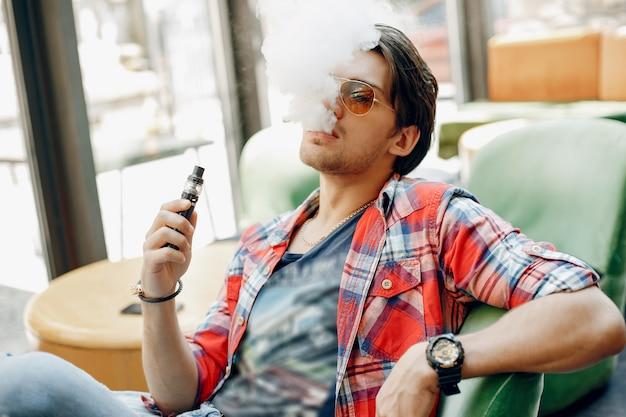 Stilvoller und eleganter mann, der in einem café mit dampf sitzt