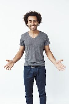 Stilvoller und gutaussehender afrikanischer mann mit weit geöffneten armen gegen weiße wand, die zu einem auftritt einlädt.