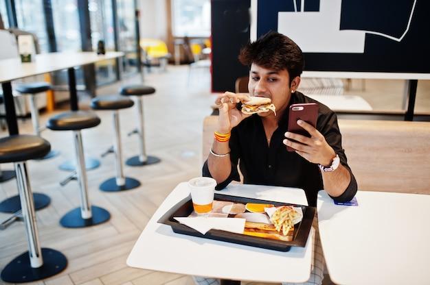 Stilvoller und lustiger indischer mann, der am schnellimbisscafé sitzt und hamburger isst und telefonisch selfie macht.