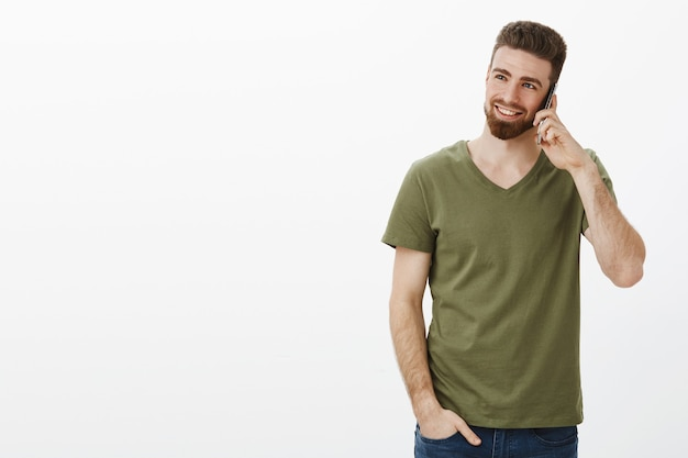 Stilvoller und selbstbewusster gutaussehender bärtiger männlicher unternehmer, der lächelnd und lachend auf dem smartphone spricht und das gespräch genießt, das die obere linke ecke über der weißen wand betrachtet
