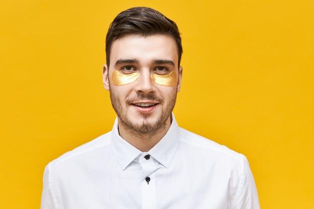 Stilvoller unrasierter junger kaukasischer mann, der augenmaske trägt, um austrocknung und dunkle ringe wegen des stressigen lebensstils zu bekämpfen, der gegen gelbe wand aufwirft,
