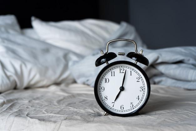 Stilvoller wecker mit glocke. die zeiger zeigen 7 stunden. zeit zum aufstehen