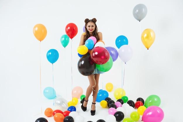 Stilvoller weiblicher hipster, der mit großen luftballons auf weiß aufwirft