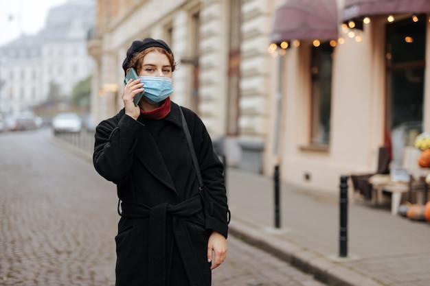 Stilvoller weiblicher hipster in der medizinischen hygienemaske, die mobile konversation beim stehen im stadtzentrum hat. prävention von infektionskrankheiten.
