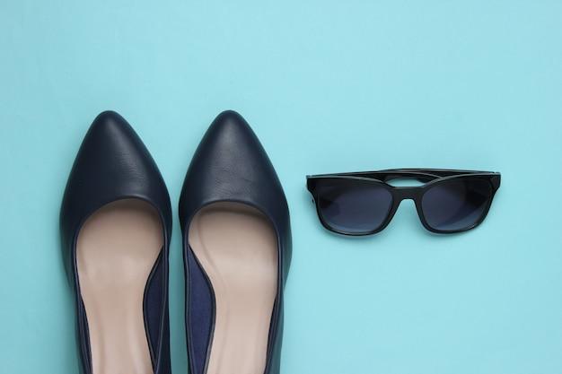 Stilvoller weiblicher look lederschuhe mit hohem absatz und sonnenbrille auf blauem grund