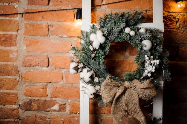 Stilvoller weihnachtskranz verziert mit weißen spielwaren und blumen