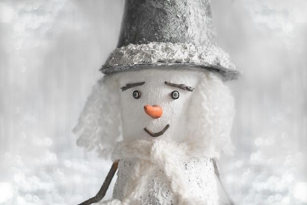 Stilvoller weihnachtsschneemann in einem grünen hut, schal, mit dem haar