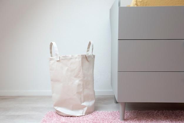 Stilvoller weißer wäschekorb, der in einem modernen raum steht moderne retro skandinavische dekoration neues zuhause