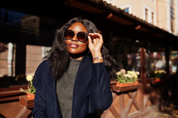 Stilvolles afroamerikanermädchen im blauen mantel und in der sonnenbrille stellte am sonnigen herbsttag auf. afrika modellfrau.