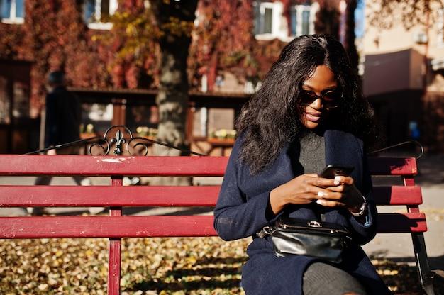 Stilvolles afroamerikanermädchen im blauen mantel und in der sonnenbrille stellte am sonnigen herbsttag auf bank und unter verwendung ihres handys auf. afrika-modellfrau mit smartphone.