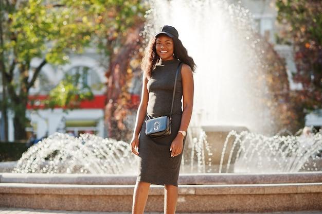 Stilvolles afroamerikanermädchen in der grauen tunika, in der umhängetasche und in der kappe stellte sich am sonnigen herbsttag gegen brunnen auf. afrika modellfrau.