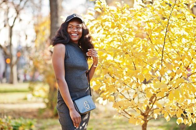 Stilvolles afroamerikanermädchen in grauer tunika, umhängetasche und kappe, die am sonnigen herbsttag gegen gelbe blätter gestellt werden. afrika modellfrau.