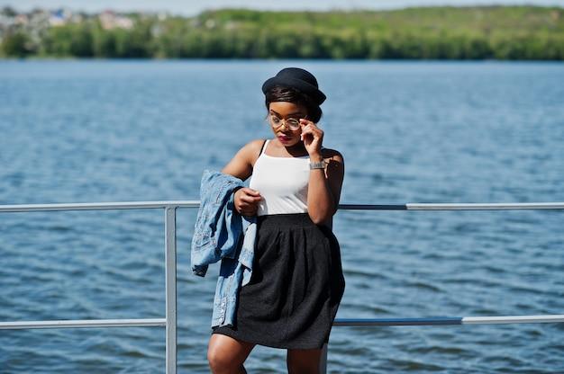 Stilvolles afroamerikanermodell im glashut, in der jeansjacke und im schwarzen rock warf im freien auf pier gegen see auf.