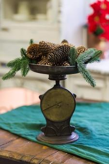 Stilvolles antikes dekor mit tannenzapfen. eine handvoll tannenzapfen auf einer antiken bronzeschuppe
