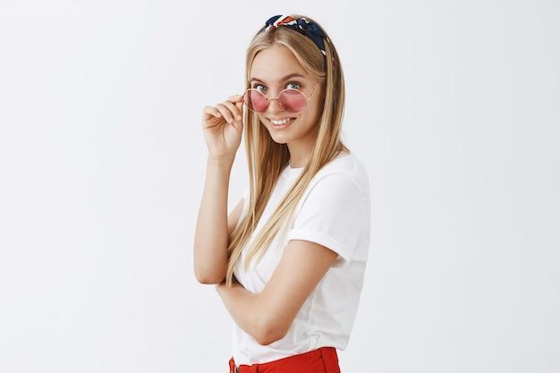 Stilvolles attraktives junges blondes mädchen, das gegen die weiße wand aufwirft