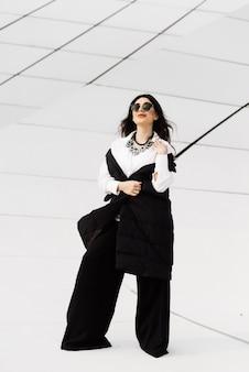 Stilvolles attraktives mädchen in schwarzem anzug und sonnenbrille, das durch die stadt baku in aserbaidschan geht