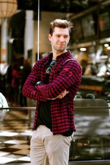 Stilvolles außenporträt des stilvollen hipster-mannes, der auf der straße aufwirft, kluger lässiger stil, getönte farben.