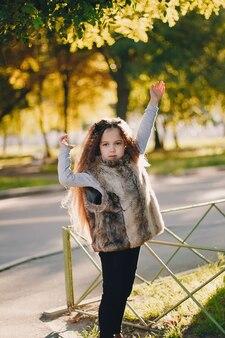 Stilvolles babymädchen 4-5 jahre alt, das stiefel trägt, pelzmantel, der im park steht. blick in die kamera. herbst-herbst-saison
