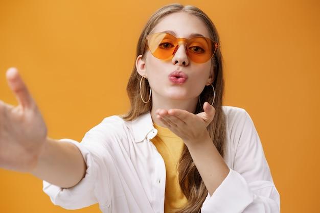 Stilvolles, beliebtes mädchen, das luftkuss an die kamera sendet, das selfie macht oder vlog aufnimmt, das als freiberuflicher reiseberater arbeitet und bilder vor orangefarbenem hintergrund macht, zart und weiblich, die hand nach vorne ziehen.