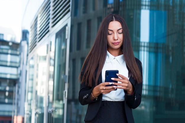 Stilvolles bezauberndes mädchen oder junge geschäftsfrau, die eine mitteilung oder sms an ihrem handy schreiben oder simsen. schöner weiblicher schauender smartphone, plaudernd im social media.