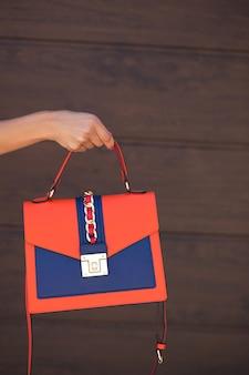 Stilvolles blau mit orangefarbener damen-ledertasche.