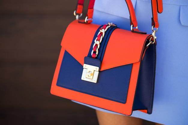 Stilvolles blau mit orangefarbener ledertasche. das mädchen hält in der hand. tasche nah oben.