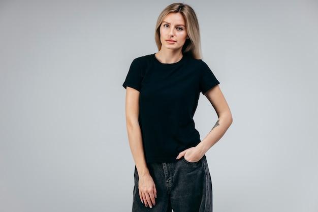 Stilvolles blondes mädchen, das schwarzes t-shirt posierend aufwirft