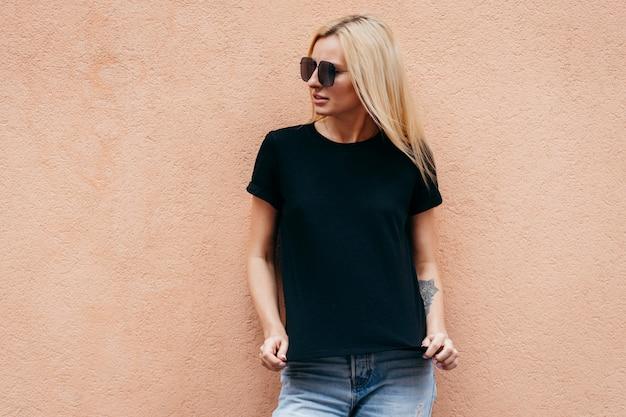 Stilvolles blondes mädchen, das schwarzes t-shirt und brille trägt, die gegen wand aufwirft