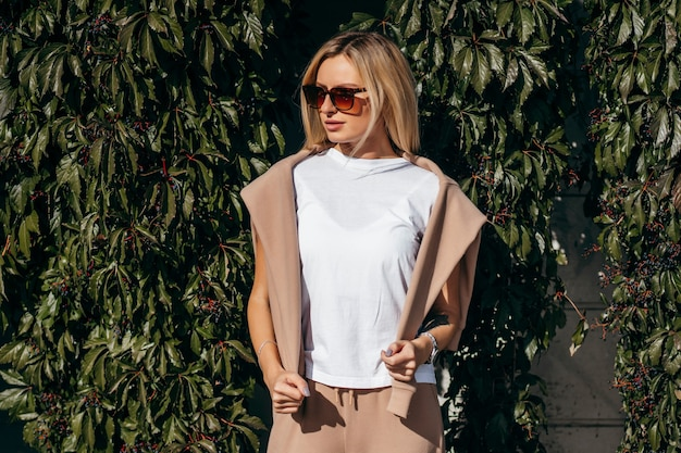 Stilvolles blondes mädchen, das weißes t-shirt und brille trägt