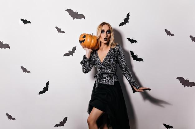 Stilvolles blondes mädchen im schwarzen kleid, das an der hexenparty aufwirft. elegantes weibliches modell mit dunklem make-up, das großen halloween-kürbis hält.